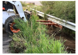 Modified Skid Steer removing debris from underneath guardrail