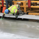 Image is of two construction workers in neon vests sitting on a platform above freshly poured concrete, which they are working on treating.