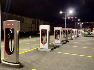Image of a row of Tesla Superchargers in a parking lot. The chargers are rectangular with plugs resembling gas pumps inside the hollow rectangle.