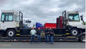 Four men stand smiling in front of a trailer with two small white truck-like vehicles on them, the electric yard tractors that were just delivered to this facility.