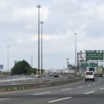 Image of a highway with two cars driving on it, in the distance the erector-set outline of the Pulaski Skyway can be seen.