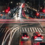 Image of an intersection at night, a long exposure has made the cars driving by appear as lines of light